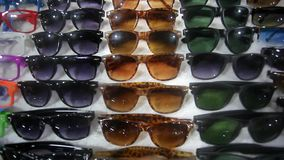 Colorful Sunglasses on sale at the city market. HD stock video footage