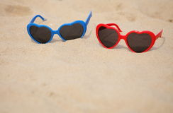 Colorful sunglasses shaped heart on the sand Stock Photos