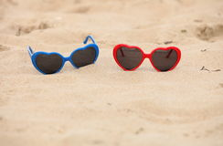 Colorful sunglasses shaped heart on the sand Royalty Free Stock Images
