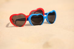 Colorful sunglasses shaped heart on the sand Stock Photo