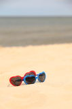 Colorful sunglasses shaped heart on the sand Stock Images