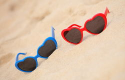 Colorful sunglasses shaped heart on the sand Stock Image