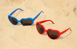 Colorful sunglasses shaped heart on the sand Royalty Free Stock Image