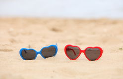 Colorful sunglasses shaped heart on the sand Royalty Free Stock Photography