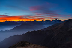 Colorful sunlight behind majestic mountain peaks of the Italian - French Alps, viewed from distant. Fog and mist covering the vall Royalty Free Stock Image