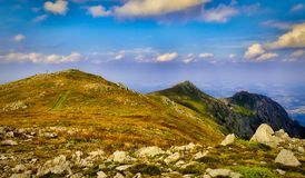 Rocky Mountain Peaks under Blue Sky with White Clouds panoramic. A colorful sunny panoramic scenery of three rocky mountain peaks Todorini kukli peaks, the royalty free stock photo