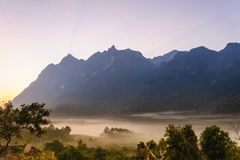 Colorful sunrise back the mountains. Fog in the valley. Royalty Free Stock Photography