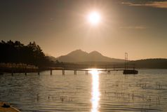 Colorful sunrise at coastal, abandoned wharf. Island with stronghold at horizon. Royalty Free Stock Image