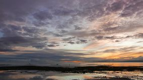 Colorful Sunrise 44. An overcast, colorful sunrise video from Dumaguete City shores. Locals can be seen gathering shells from the shallow pools left behind by stock footage