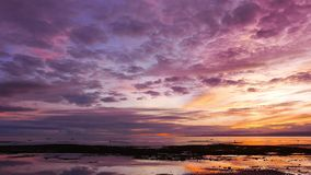Colorful Sunrise 43. An overcast, colorful sunrise video from Dumaguete City shores. Locals can be seen gathering shells from the shallow pools left behind by stock footage