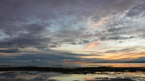Colorful Sunrise 45. A pale yet colorful sunrise video from Dumaguete City shores. Locals can be seen gathering shells from the shallow pools left behind by the stock footage
