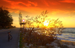 Colorful sunrise,road and bike on the seashore. Wonderful day start on the seashore, sunrise, bicycle, colorful sky.Picture taken on November 6th, 2013, Black Stock Image