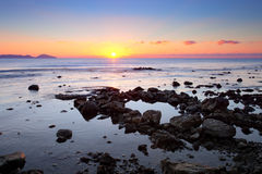 Colorful sunrise on the rocky coast Stock Photos