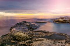 Colorful sunrise skyline viewed from the rocky beach. Royalty Free Stock Image