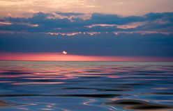 Colorful sunset. Over smooth waves striking colors Royalty Free Stock Image