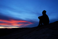 Colorful Sunset at Arches National Park. A young woman enjoys a spectacular sunset full of pink and blue at Arches National Park in Eastern Utah Stock Image