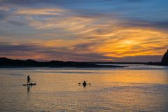 Colorful sunset as seen from the Morro Bay harbor; silhouettes of people enjoying the view from the kayak and paddle board;. California royalty free stock photography