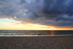 The colorful sunset on a beach on a cloudy weather. Royalty Free Stock Image