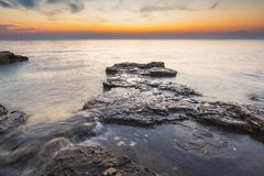 Enjoying the colorful sunset on a beach with rocks on the Adriatic Sea coast Istria Croatia. Colorful sunset on a beach with rocks on the Adriatic Sea coast stock photography