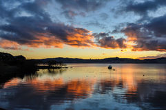 Colorful sunset with a boat  in Lake Taupo, New Zealand Royalty Free Stock Photo