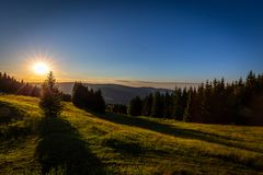 Colorful sunset from Cernava to Ramzova with dark blue sky, green grass and trees in Jeseniky royalty free stock photo