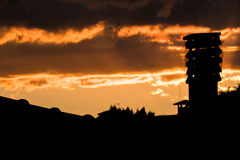 Colorful sunset with chimney silhouette on a roof house over. Royalty Free Stock Images
