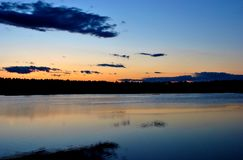 Colorful Sunset and Clouds. Dark indigo clouds reflecting on calm waters at sunset wiht trees in the background Royalty Free Stock Photos