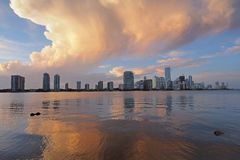 Colorful sunset cloudscape over Miami. A very colorful cloudscape over the City of Miami skyline reflected on the calm waters of Biscayne Bay, Florida royalty free stock photography