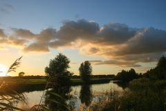 Colorful sunset with cumulus clouds over a small lake near Gouda, The Netherlands stock images
