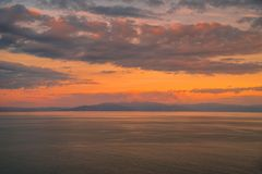 Colorful sunset with dramatic sky background over sea stock photography
