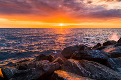 Colorful sunset in the evening over the ocean Stock Photos