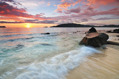 Colorful Sunset and Flowing wave on a Beach. Stock Photos