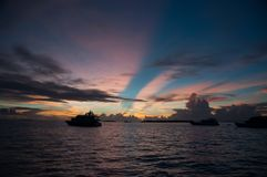 A colorful sunset on the Indian Ocean: pink yellow and blue glare in the sky, the contours of the ships in the middle of the wave,. Colorful sunset on the Indian Royalty Free Stock Images