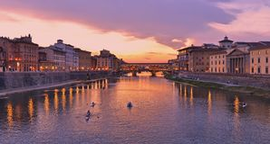 Colorful sunset with lights on Ponte Vecchio bridge in Florence, Italy. Colorful sunset with lights on Arno river, small boats and Ponte Vecchio bridge in royalty free stock photo