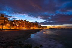 A colorful sunset on the Mediterranean Sea overlooking the cozy Port Saplaya area in Valencia. Spain stock photo