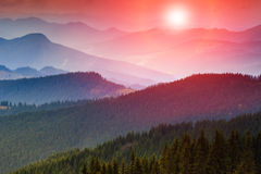 Colorful sunset in the mountains. Dramatic overcast sky Stock Image