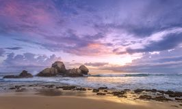 Colorful sunset at the ocean shore. Colorful sunset at the beach of Indian ocean; boulders in the water; golden surf lines stock images