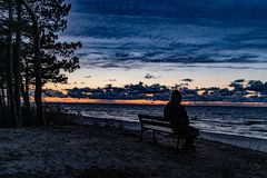Free Colorful Sunset On The Sea Observed By A Man In A Cap Sitting On A Black Bench On A Dune Stock Photo - 163909520