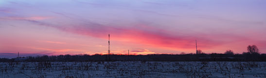 Colorful sunset over blue snow field panorama. Colorful sunset over the blue snow field panorama Royalty Free Stock Image