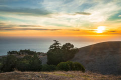 Colorful sunset over California ocean, rolling hills Stock Images