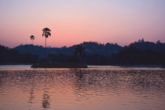 Colorful sunset over the Kandy Lake with silhouettes of palmtrees Royalty Free Stock Photography