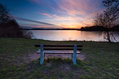 Colorful sunset over lake shore with bench Royalty Free Stock Photos