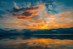 Colorful sunset over a mountain lake. Surrounded by forests and beautiful reflections Royalty Free Stock Photos