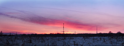 Colorful sunset over the snow field wide panorama Stock Photo