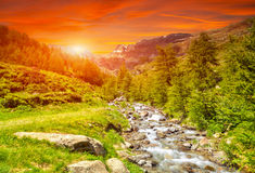 Colorful sunset and a river in the Alps Stock Photos