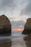Colorful sunset between rocks cliffs on beautiful sandy beach in algarve Royalty Free Stock Photos