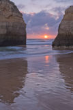 Colorful sunset between rocks cliffs on beautiful sandy beach in algarve Stock Photo