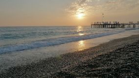 Colorful sunset. Sea view with waves and foam, pier and pebble beach stock video footage