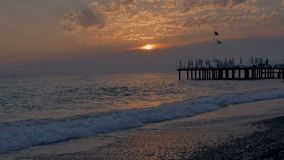 Colorful sunset. Sea view with waves and foam, pier and pebble beach. time lapse. stock video