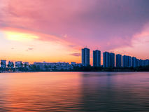 Colorful sunset sky in the city reflecting on the water. Surface Royalty Free Stock Photo